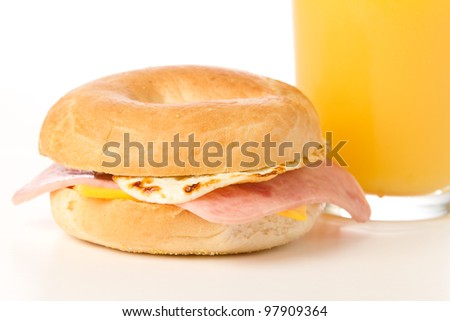 Egg Sandwich / This is a photo of a delicious egg, ham and cheese Sandwich on a toasted bagel with a glass of orange juice. - stock photo