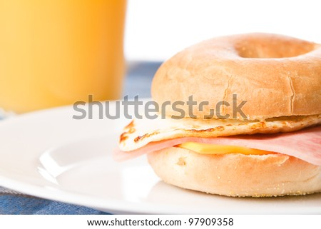 Egg Sandwich / This is a photo of a delicious egg ham and cheese sandwich on a toasted bagel with a glass of juice in the background. - stock photo