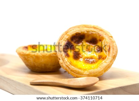 Egg tarts and wooden spoons on wooden plate - stock photo