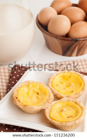 Egg tarts sweet custard pie desserts with eggs and milk in background. - stock photo