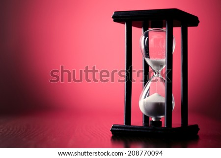 Egg timer or hourglass on a graduated red background with copyspace in a conceptual image of passing time and time management - stock photo