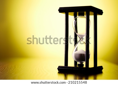 Egg timer or hourglass on a graduated yellow background with copyspace in a conceptual image of passing time and time management