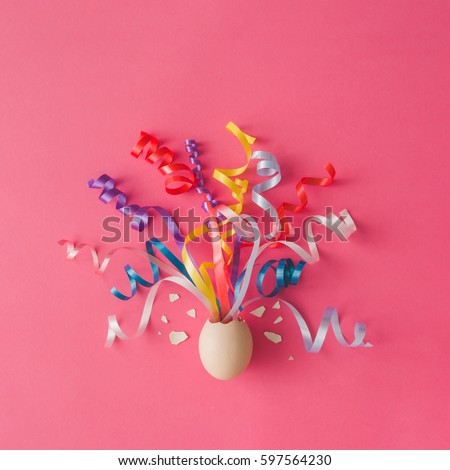 Egg with party streamers on pink background. Easter concept. Flat lay.