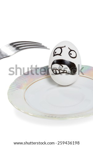 Egg with smiley lies in the plate and yells of fright because of approaching a fork isolated on a white background - stock photo