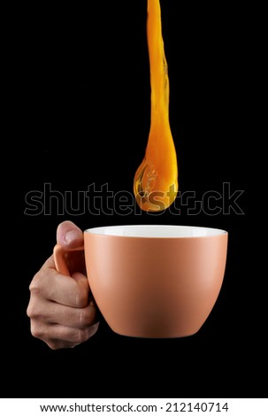 Egg Yolk dripping, falling in to cup, on black background.