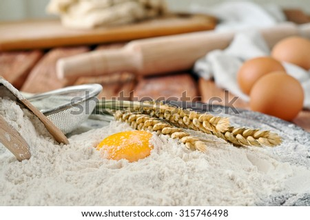 Egg yolk in flour closeup on a wooden board in a bakery. Rural or rustic style. Copy space. Free space for text