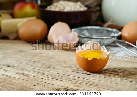 Egg yolk on a wooden table in a rustic kitchen closeup. Food background - stock photo