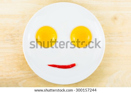 Egg yolks and red chili on a white plate on a wooden table, A smiling face. - stock photo