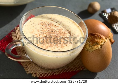 Eggnog cupcake baked in eggshell and eggnog drink on the side, photographed with natural light (Selective Focus, Focus on the front of the cupcake and the middle of the drink) - stock photo
