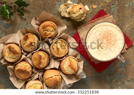 Eggnog cupcakes baked in eggshell and eggnog drink in glass cup, photographed overhead with natural light (Selective Focus, Focus on the top of the cupcakes and the drink) - stock photo