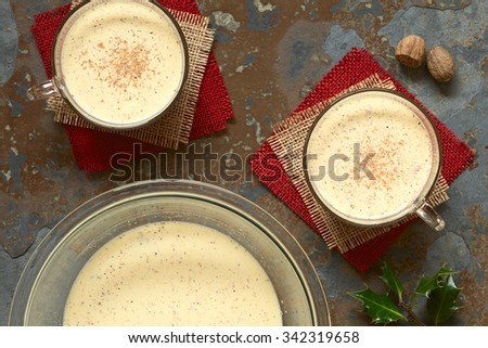 Eggnog drink in bowl and in two glass cups with ground nutmeg on top, photographed overhead on slate with natural light - stock photo