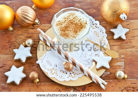 Eggnog with cinnamon  and homemade christmas cookies with sugar frosting - stock photo