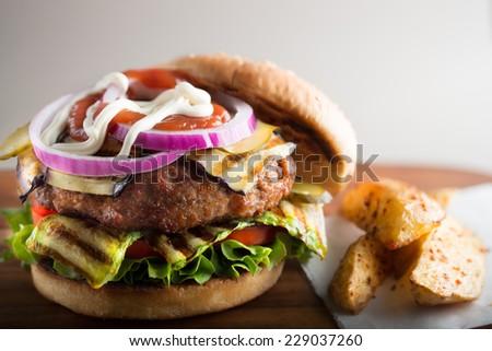 eggplant and zucchini hamburger on wooden table - stock photo