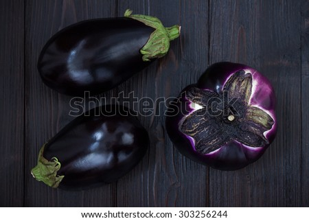 Eggplant (aubergine) on dark wooden table. Top view. Fresh raw farm vegetables - harvest from the garden in rustic kitchen. Rural still life from above - stock photo