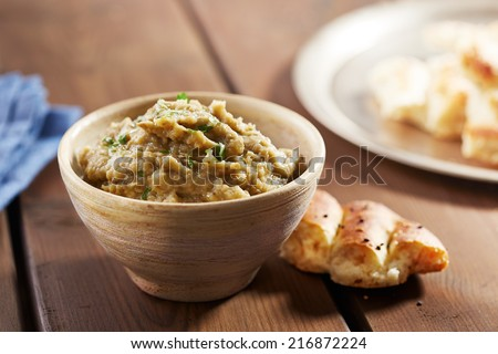 Eggplant baba ganoush with flat bread and herbs - stock photo
