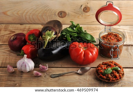 eggplant caviar in a glass jar ingredients: eggplant, tomato, pepper, onion, garlic on a wooden rustic background - top view