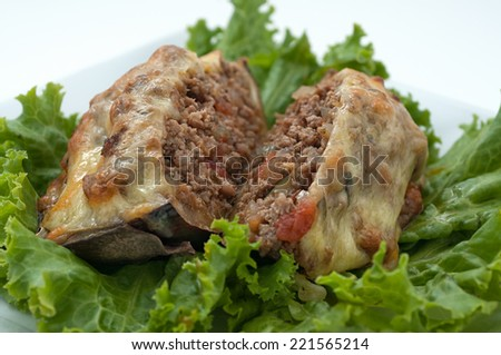 Eggplant filled witn minced meat on lettuce leaves - stock photo