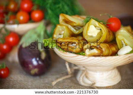 Eggplant rolls with cheese and garlic on a wooden saucer - stock photo