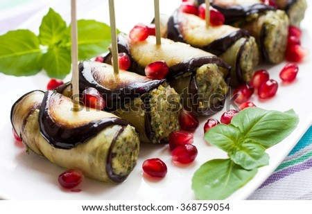 Eggplant rolls with nuts. Delicious starter of fried aubergines with nuts, herbs and pomegranate seeds. Dish of Georgian cuisine  - stock photo