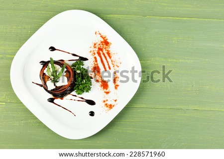 Eggplant salad with tomato and feta cheese on plate, on wooden background - stock photo