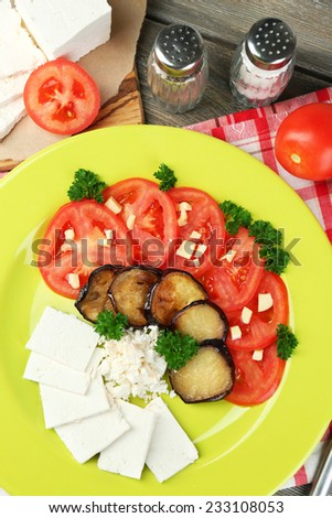 Eggplant salad with tomatoes and feta cheese, on napkin, on wooden background