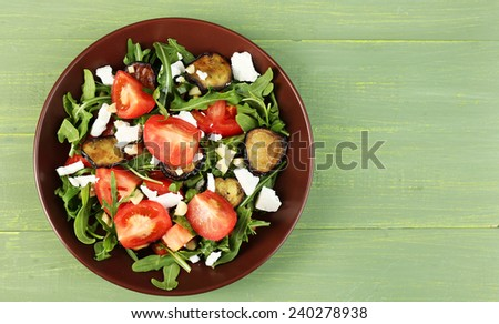 Eggplant salad with tomatoes, arugula and feta cheese, on wooden background - stock photo