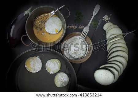 Eggplant slices, dipped in egg and flour and put to fry in frying pan with olive oil. Top view shot. - stock photo