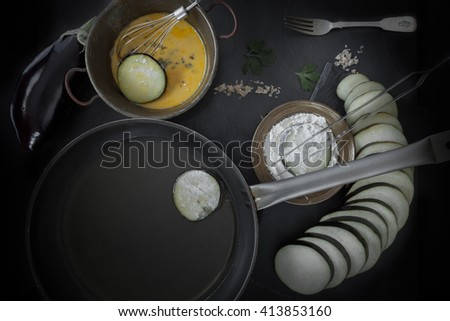 Eggplant slices, dipped in egg and flour and put to fry in olive oil in frying pan. Top view shot. - stock photo