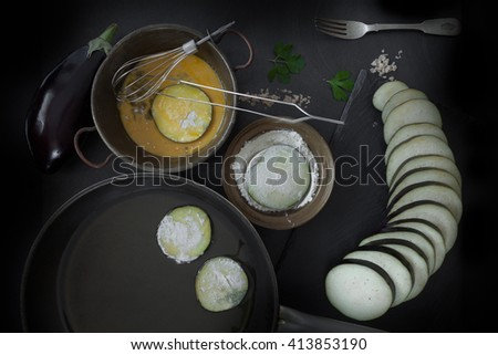 Eggplant slices, dipped in egg and flour and put to fry in olive oil in frying pan. View from above. - stock photo