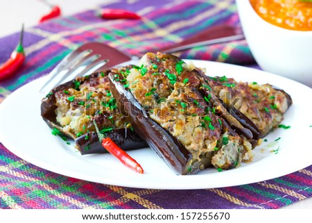 Eggplants stuffed with meat and vegetables, traditional Italian dish on plate with sauce - stock photo