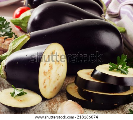 Eggplants with fresh  herbs on wooden board. Selective focus - stock photo