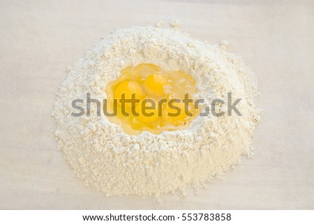 eggs and flour on the wooden board to made pasta
