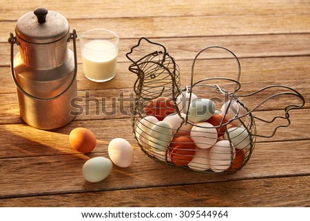 Eggs and milk in a vintage hen shape basket on wood with blue easter white and brown - stock photo