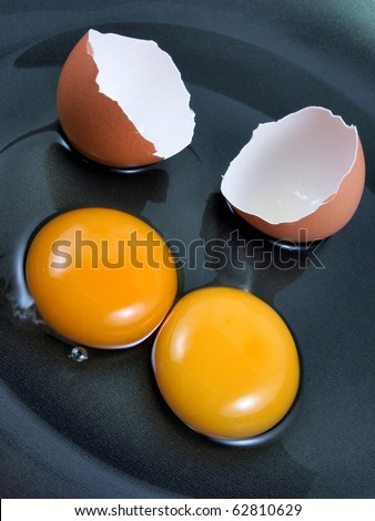 Eggs and shell cracked on a black pan - stock photo
