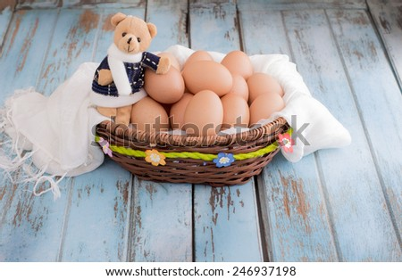 Eggs and teddy bear is isolated on wooden table. - stock photo