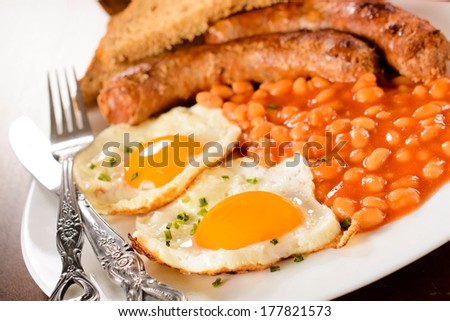 Eggs,beans and sausage in the plate.Selective focus on the front egg