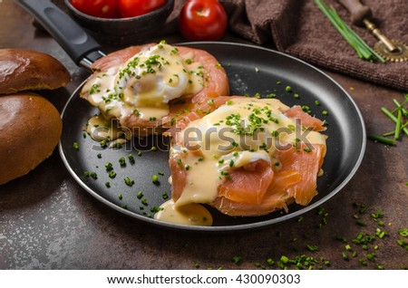 Eggs benedict and smoked salmon on a toasted bun, topped with hollandaise sauce