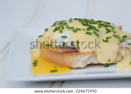 Eggs Benedict toasted English muffins ham poached eggs and delicious buttery hollandaise sauce - stock photo