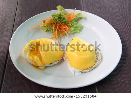 Eggs Benedict- toasted English muffins, poached eggs, and delicious buttery hollandaise sauce - stock photo