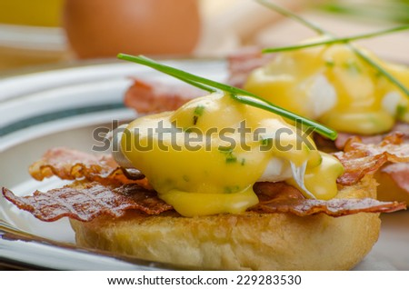 Eggs bvenedict with chives and fresh juice, spinach leaves, bio eggs - stock photo