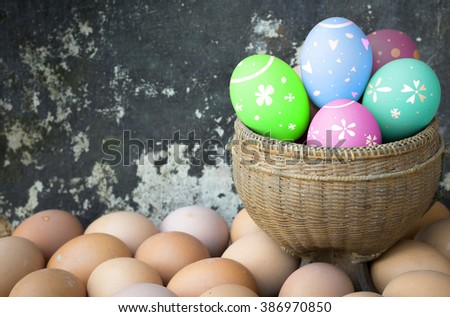 Eggs chicken fresh in a basket on wooden background, Painted Easter eggs background. - stock photo