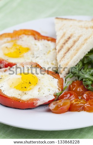 Eggs fired in bell pepper frames with cherry tomatoes and arugula
