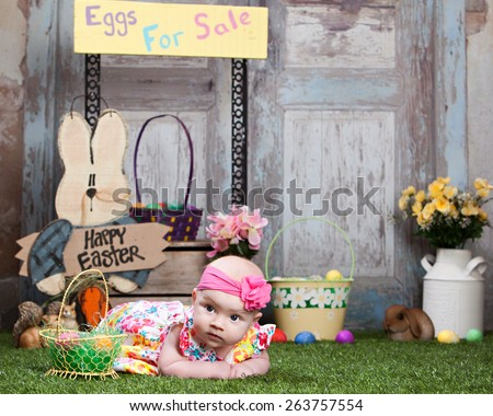 Eggs for sale.  Adorable baby lying in the grass with Easter decor in the background.  Room for your text. - stock photo