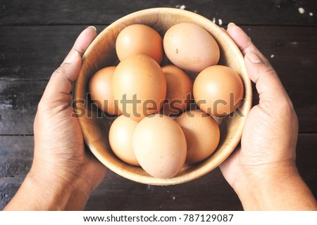 Eggs in a bowl with hand