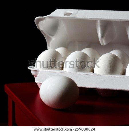 Eggs in a box on the Red surface. Black background