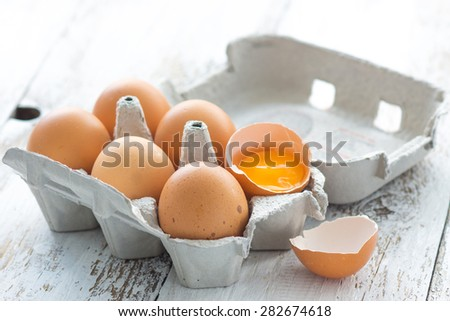 Eggs in a carton on a wooden background - stock photo
