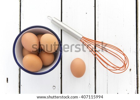 Eggs in a ceramic bowl with a whisk on a rustic white painted wood table top shot from above