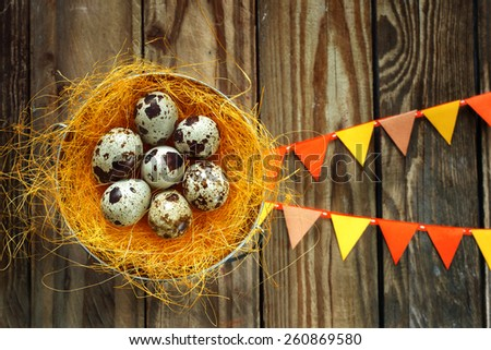 eggs in a nest on a wooden table, easter decoration - stock photo