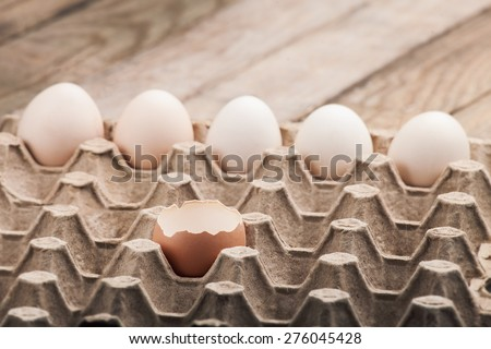 Eggs in a paper tray on a wooden table from boards, with the split egg in the foreground, nobody. - stock photo