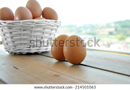 eggs in a white wicker basket on wooden table